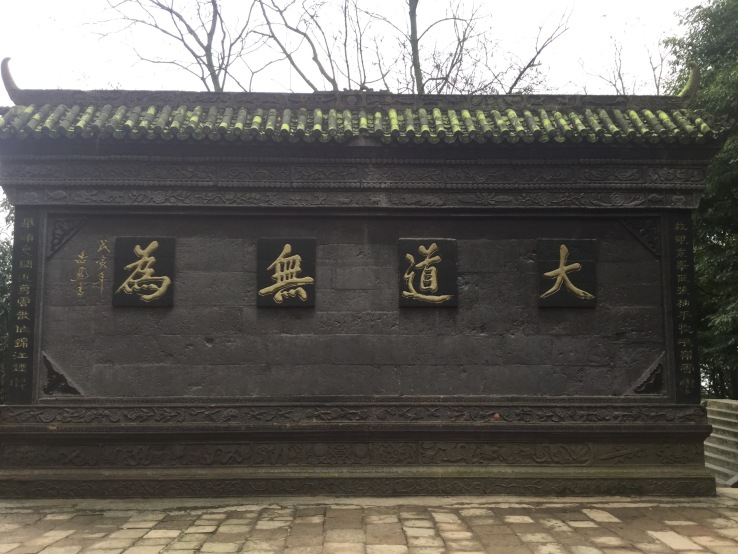 You have to read the words from right to left. The phrase was written in traditional Chinese, and it means the greatest virtue is to do nothing (my own translation haha). It is central to Daoism in China.